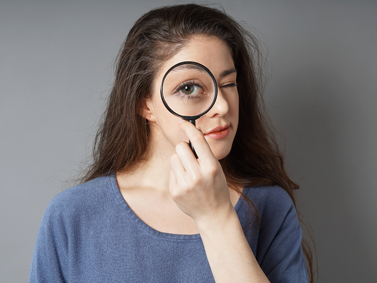 young-woman-looking-through-magnifying-glass-detec-A2DB389